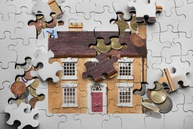 Jigsaw puzzle house spilling coins and notes
